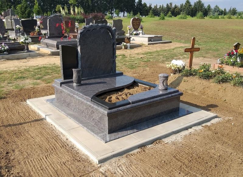 Vizag Blue/Zimbabwe színösszeállítású különleges gránit síremlék, gömbölyített borítással, fedlapján íves ültetőrésszel, faragott fatörzses és gravírozott dupla emlékkel