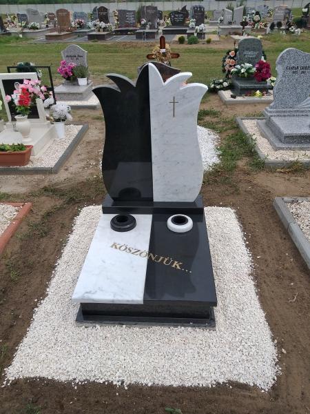 Fekete-fehér színösszeállítású egyedi urna síremlék, tulipán formájú emlékrésszel, fedlapján kontrasztos két süllyesztett vázával