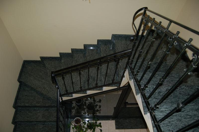 U alakú lépcsőház travertinre várott Olive Green gránittal burkolva