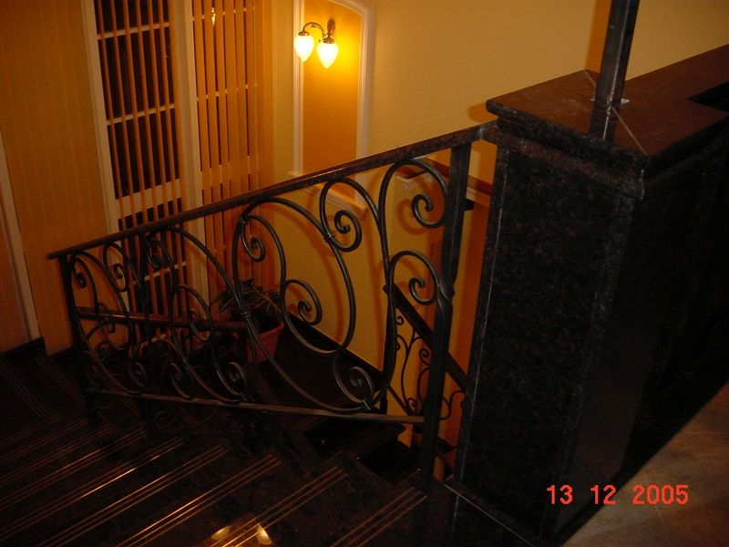 Tan Brown gránit lépcső rézcsúszásgátlóval, kovácsoltvas korláttal, emeleti érkező részengránit posztamensekkel, illetve gránit baluszteres korláttal