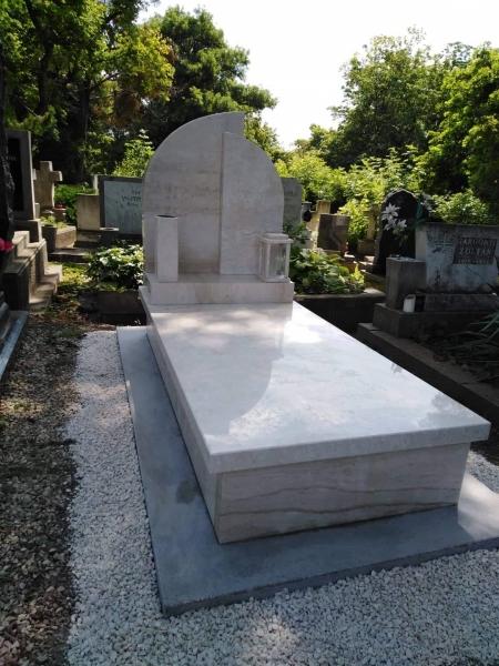 Szimpla mészkő síremlék dupla, íves emlékrésszel, a lépcsőrészen vázával és mécsestartóval