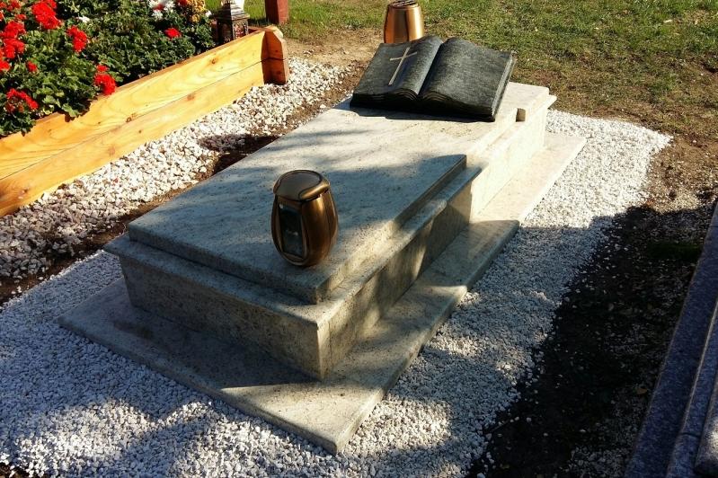 Szimpla fedett gránit sírkő, keretborítással, ráültetett fedlappal, nyitott könyv emlékrésszel és bronz kiegészítőkkel